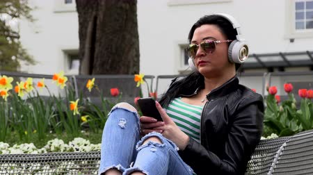 senta : Brunette sits on a street bench and listens to music