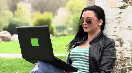 mladé ženy : Brunette on the grass with a computer