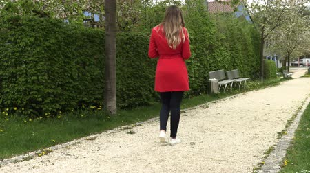 benches : Girl in a red dress with a phone on the street in the park Stock Footage
