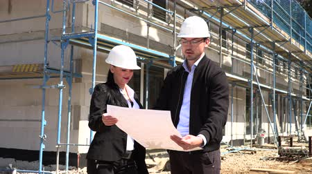 прораб : Two architects in white helmets discuss a plan at a construction site