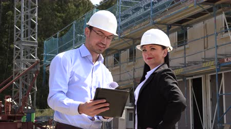 feliz : Two architects a man and a woman in construction in white helmets
