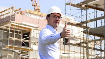 feliz : Architect at the construction site shows thumbs up
