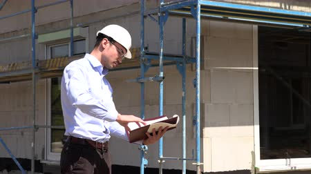 inspectie : Architect inspects construction outside talking on the phone Stockvideo