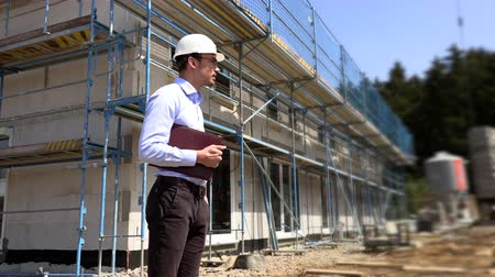 hard hat : Architect inspects construction outside talking on the phone Stock Footage