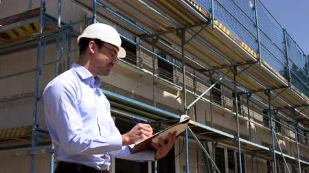blueprint : Architect inspects construction outside talking on the phone Stock Footage