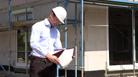жилет : Architect inspects construction outside talking on the phone Стоковые видеозаписи