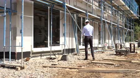 müfettiş : Architect inspects construction outside talking on the phone Stok Video