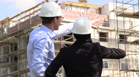 védősisak : Two architects a man and a woman in construction in white helmets