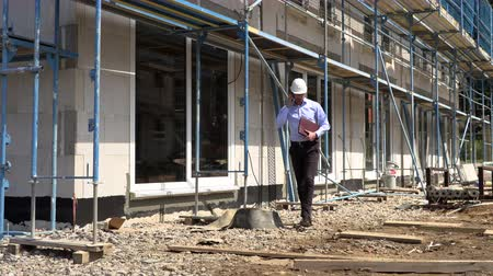 yelek : Architect inspects construction outside talking on the phone Stok Video