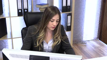 the manager writes on the computer and checks the documentation at the table. Wideo