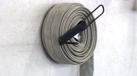 cabinet : Fire hose reeled up hanging on the wall