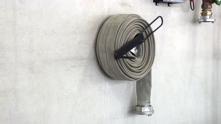 разъем : Fire hose reeled up hanging on the wall