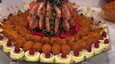 shellfish : Boiled crayfish and crab sticks with fruit laid out on a tray Stock Footage
