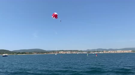 tourists fly by parachute over the sea