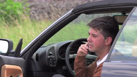 členění : A young man sits in a broken car and makes phone calls
