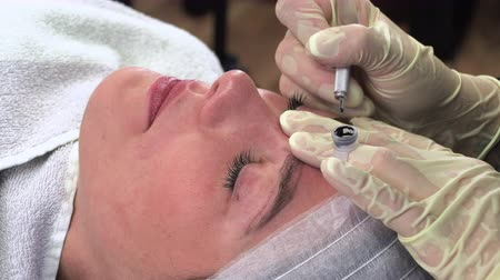 permanente : Young girl make permanent makeup. Eyebrow Microblading