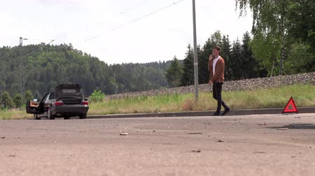 sós : A young man is calling on the phone near a broken car Stock mozgókép