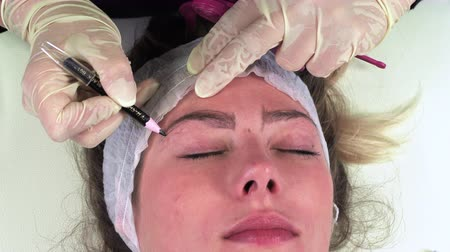 pigmento : Young girl make permanent makeup. Eyebrow Microblading