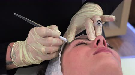 microblading : Microblading,Woman having eyebrows drawn and tinted with pencil.