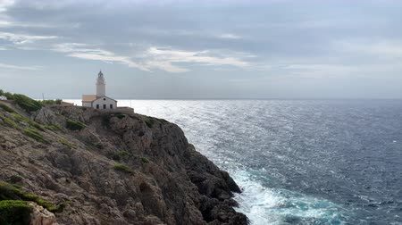 Майорка : Lighthouse on a rocky shore in the bay of Mallorca