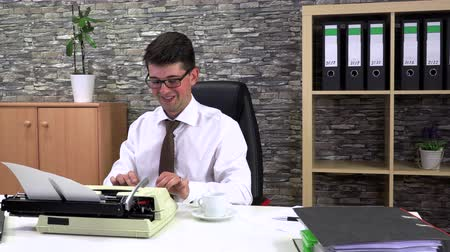 Office worker writes on a typewriter