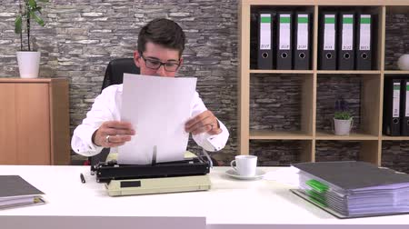 strojopis : accountant writes on a typewriter at a table in the workplace