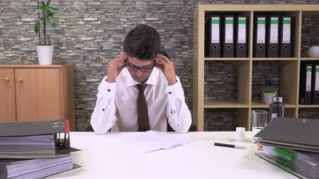 мигрень : an accountant in an office suffers a headache Стоковые видеозаписи