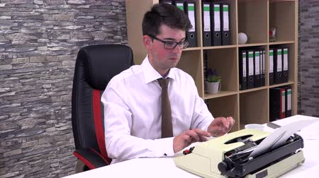 máquina de escrever : accountant writes on a typewriter at a table in the workplace