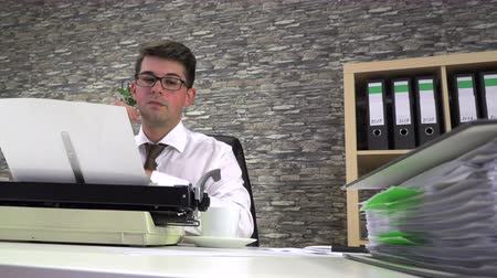 типы : accountant writes on a typewriter at a table in the workplace