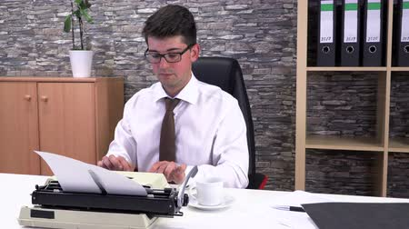 levelezés : Office worker writes on a typewriter