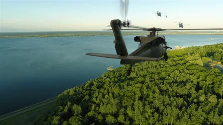 brezilya : Helicopters Blackhawk fly over the river bank, flying into the horizon