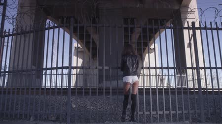 sombrio : Beautiful girl staying and positing near the fence under the bridge. Industrial area fashion videoshoot Vídeos