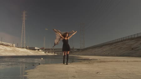 dekarz : Beautiful girl with the waving fabric positing, dancing, running, walking in the LA River. Industrial area fashion videoshoot.