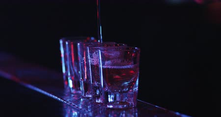 nightcap : Barman pouring drinks into glasses on bar table. Lounge bar atmosphere. Bartender Pouring Alcoholic Drink into Shot Glasses. Slow motion, Macro Close up Stock Footage
