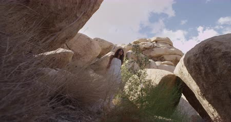 отходы : Girl walking in the desert through the rocks and caves. Mojave desert views. Slow motion Стоковые видеозаписи