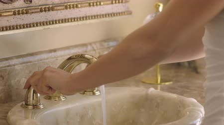 tuvalet : Female hands washing under running water in a sink. Tap water. Classy bathroom in the luxury house Stok Video