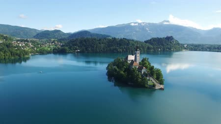 девственница : AERIAL VIEW: flight over Lake Bled in Slovenia .View of the Church of the Assumption of the Virgin Mary Стоковые видеозаписи