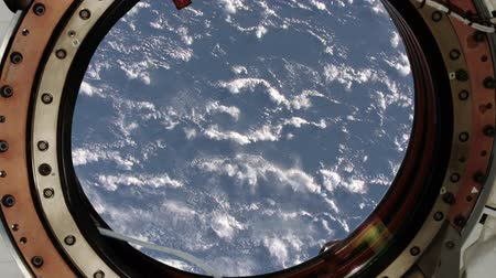 collaboration : View of earth through the porthole of the International space station.