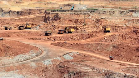 экскаватор : Mining dump trucks and excavators in the open pit mine Стоковые видеозаписи