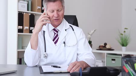 physicians : Doctor chatting on his mobile phone while seated at his desk in his office reading information on the screen, of his laptop computer. Stock Footage