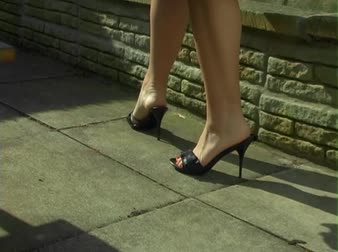 латина : A Latina woman walks back and forth in sexy black Italian high heels in garden courtyard (shows legs heels and tanned skin color)