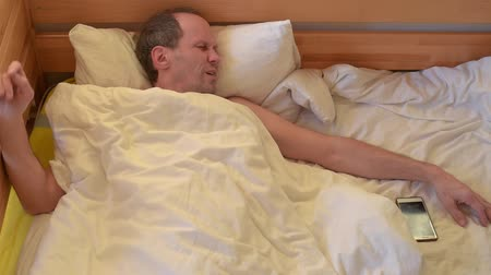 wakeup : Tired man lying in bed and receiving message at morning