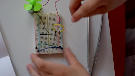 construtor : Young boy making electrical circuit with blower at home, closeup video