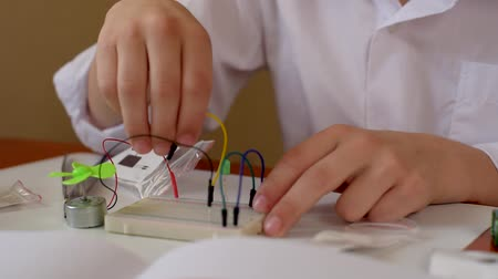 construtor : Closeup of young boy assembling electrical circuit with blower