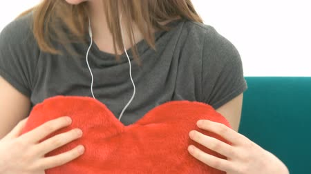 fejhallgató : Pretty Woman listening to music and cuddling with a heart pillow Stock mozgókép
