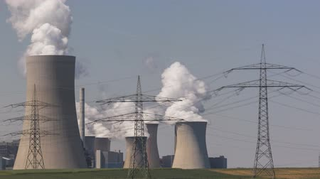 climate : Timelapse of brown coal power plant with huge cooling towers and steam and powerlines
