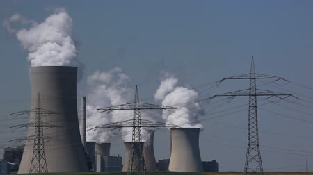 powerplant : Brown coal power plant with huge steaming cooling towers and electric towers Stock Footage