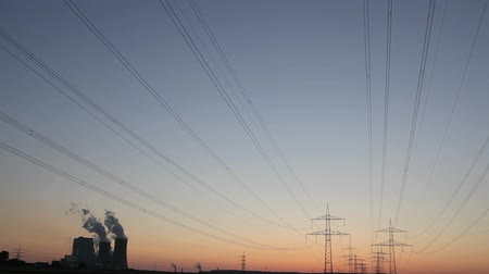 powerplant : Timelapse brown coal power plant with cooling towers and steam and powerlines during sunset with red sky Stock Footage