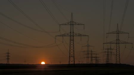 устойчивость : Sunset Timelapse of Wind Turbines behind Power Lines and a group of Power Towers Стоковые видеозаписи