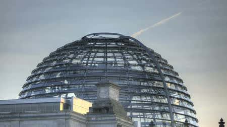 купол : Time lapse of the Glass Dome German Reichstag in Berlin during evening with an airplane leaving a contrail